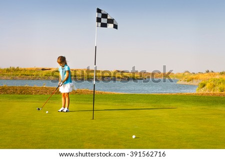 Cute little girl playing golf on a field outdoor. Summertime