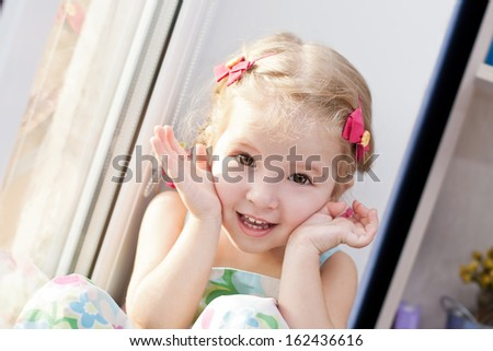 cute little girl playing hide and seek smiling looking at the camera on a white background - stock photo