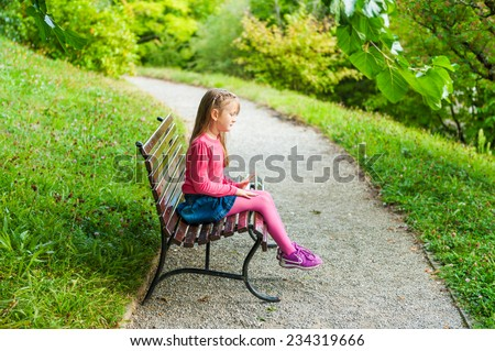 Cute little girl playing in a park, sitting on a bench on a nice sunny day, outdoors - stock photo
