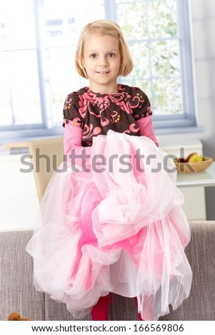 Cute little girl playing princess at home, standing on sofa, smiling.