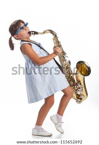 Cute little girl playing saxophone - stock photo