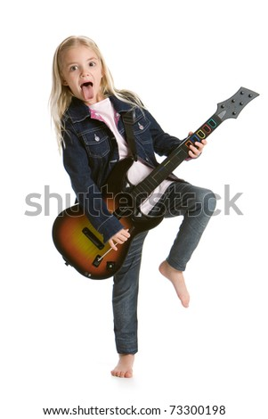 Cute little girl playing video game guitar - stock photo