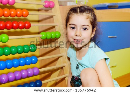 Cute little girl playing with abacus in kindergarten - stock photo
