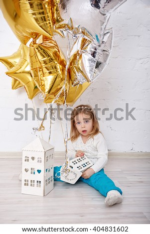 Cute little girl playing with balloons. The atmosphere of joy, fun, holiday. Birthday. - stock photo