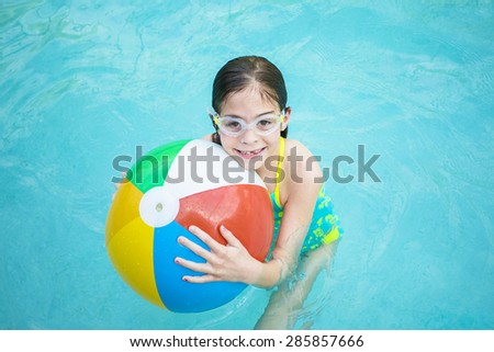 Cute little girl playing with Beach ball in a swimming pool - stock photo