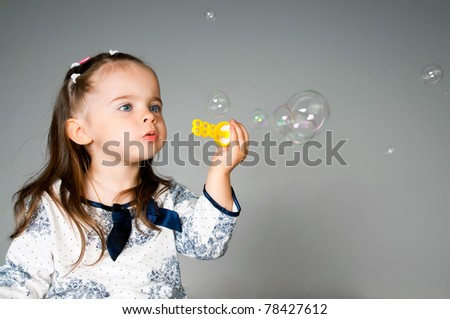 cute little girl playing with bubbles in the studio