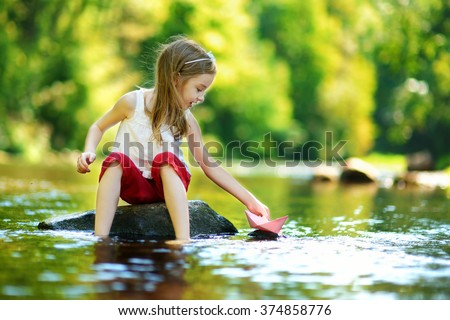 Cute little girl playing with paper boat by a river on warm and sunny summer day - stock photo