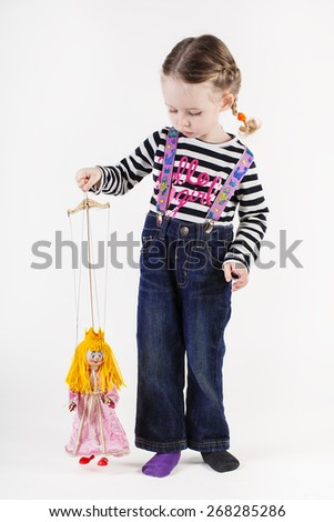 Cute little girl playing with puppet, isolated on white - stock photo