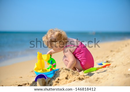 Cute little girl playing with sand at ocean beach