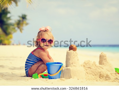 cute little girl playing with sand on tropical beach - stock photo