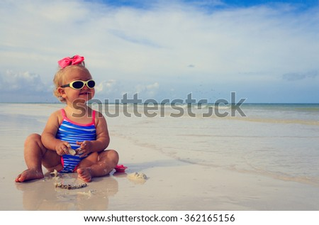 cute little girl playing with shells on beach