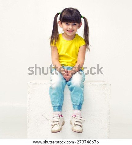 Cute little girl portrait in jeans  full length sit studio isolated on white - stock photo