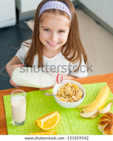 cute little girl pours milk in cereal - stock photo