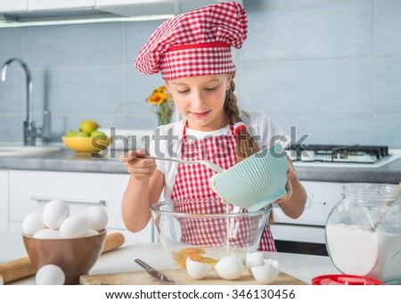 cute little girl preparing a dough with eggs and cream - stock photo