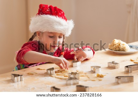 Cute little girl preparing cookies for christmas. Focus on the girls face - stock photo