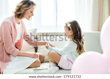 Cute little girl putting jewelry on hand of happy mother while sitting on sofa
