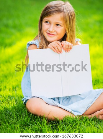 Cute little girl reading book outside on grass in backyard - stock photo