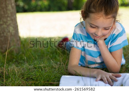 Cute little girl reading in park on a sunny day - stock photo