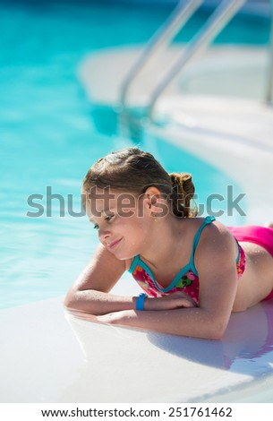 Cute little girl relaxing by the swimming pool  - stock photo