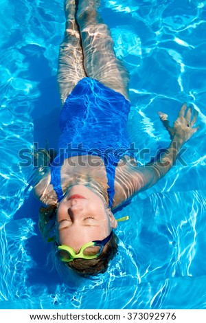 Cute little girl relaxing on water at swimming pool