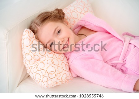 Cute little girl resting on a sofa at home. Leisure. Family concept.