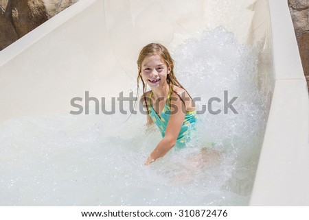 Cute little girl riding down a water slide at a water park  - stock photo