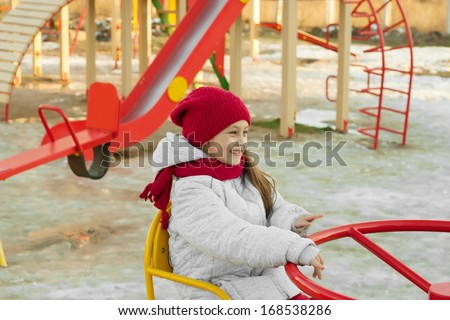 cute little girl riding on a carousel at the playground