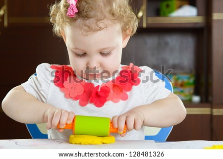 Cute little girl rolling clay dough with rolling pin - stock photo