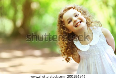 Cute little girl shone with happiness, curly hair, charming smile, sunny summer portrait - stock photo