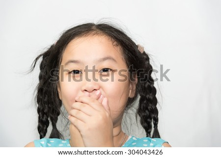 cute little girl show her feeling in a grey background and close-up. - stock photo