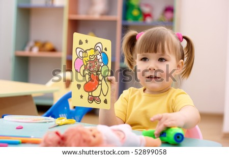 Cute little girl showing a picture in preschool - stock photo