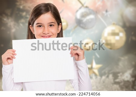 Cute little girl showing card against blurred christmas background - stock photo