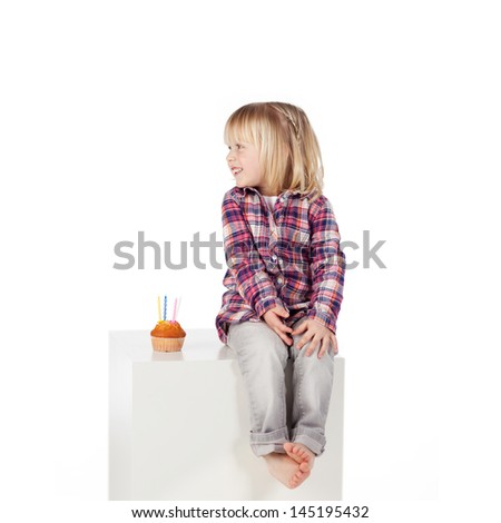Cute little girl sitting barefoot on a white cabinet with a small birthday cake with four candles alongside her, white background - stock photo