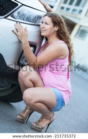 Cute little girl sitting in high heels near car bumper - stock photo