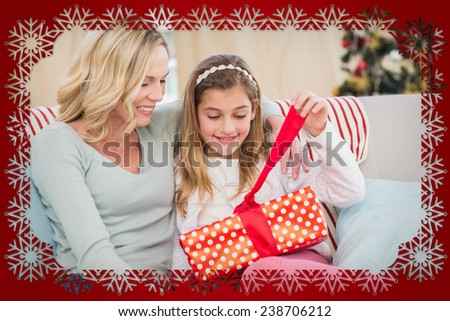 Cute little girl sitting on couch opening gift with mum against snowflake frame