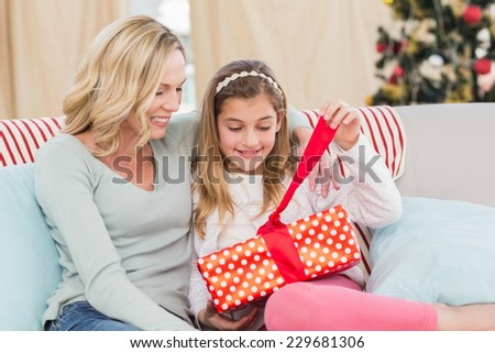 Cute little girl sitting on couch opening gift with mum at home in the living room - stock photo