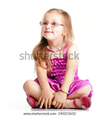 cute little girl sitting on floor and smiling, studio shot isolated on white background - stock photo