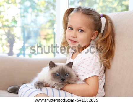 Cute little girl sitting on sofa with fluffy cat