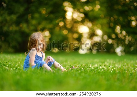 Cute little girl sitting on the grass on a sunny summer day - stock photo