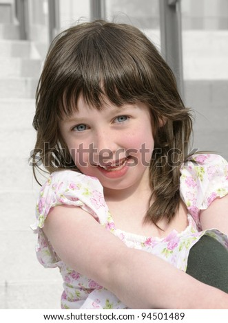 Cute little girl sitting on the steps outside her home. - stock photo