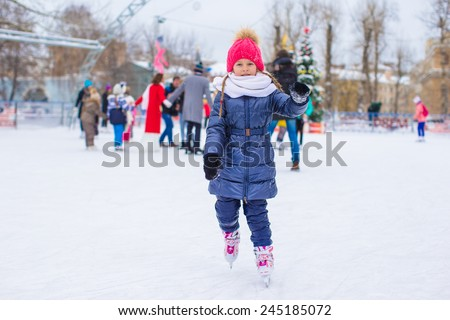 Cute little girl skating on the ice rink outdoors - stock photo