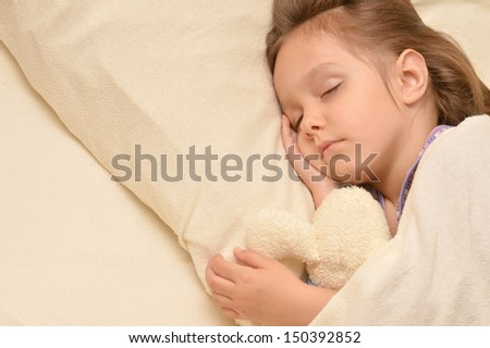 Cute little girl sleeping  in her bed - stock photo