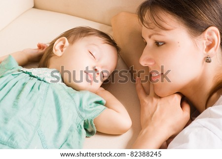 cute little girl sleeping on sofa with mom