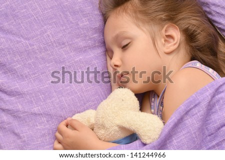 cute little girl sleeping with a toy in her bed
