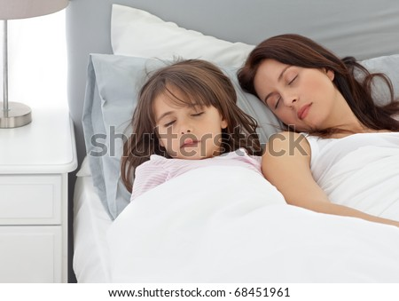 Cute little girl sleeping with her mother in the morning at home - stock photo