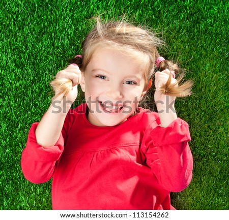 cute little girl smiling on a green lawn - stock photo