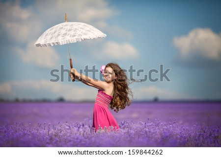 Cute little girl smiling outdoors in lavender meadow. Happy toddler girl walking in lavender flowers aromatherapy. Smiling kid portrait. Beautiful child on nature. Healthy little girl playing. - stock photo
