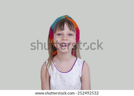 Cute little girl smiling over light grey background, milk teeth change - stock photo