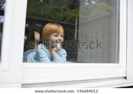 Cute little girl smiling while looking out through glass window at home - stock photo