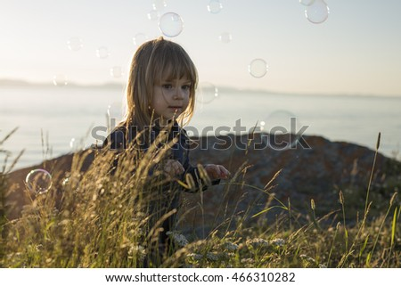 Cute little girl standing close to beach at sunset